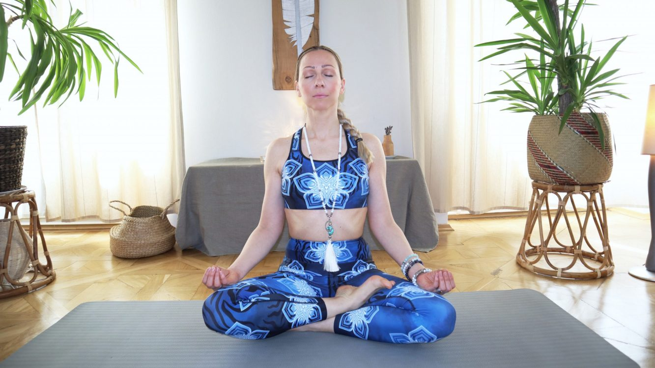 Pilates Instructor sitting in yoga lotus pose with closed eyes.