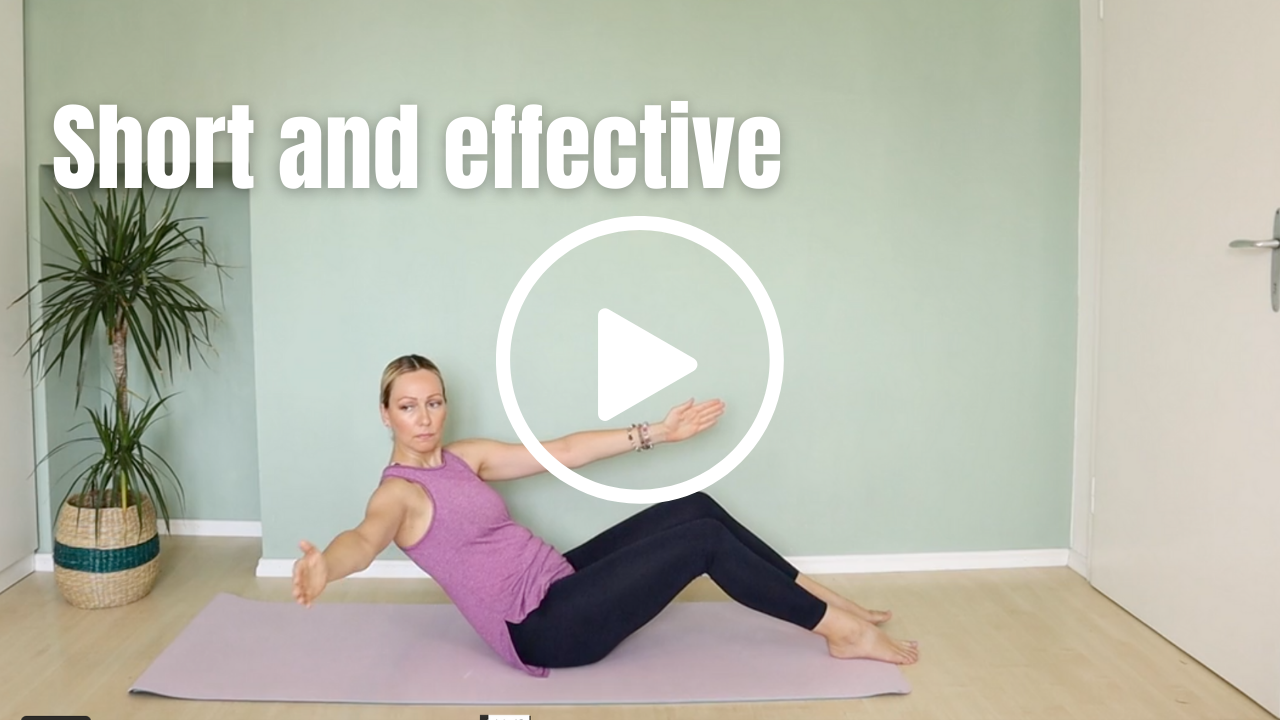 Pilates Instructor sitting on mat with bent knees and one arm reaching to side